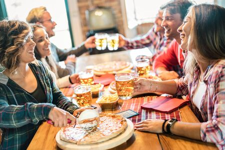 Young friends eating pizza at home on winter reunion - Friendship concept with happy people enjoying time together and having fun drinking brew pints - Cosy dinner place with focus on beer glass