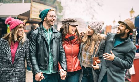 Millennial friends group walking at London city center - Next generation friendship concept on multicultural young people wearing winter fashion clothes having fun together in UK - Warm vintage filter
