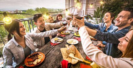 Jeunes s'amusant à griller du vin rouge ensemble lors d'un dîner dans une villa en plein air - Amis heureux mangeant un barbecue dans la terrasse du restaurant - Concept de style de vie millénaire sur un filtre rétro chaleureux - Vue large