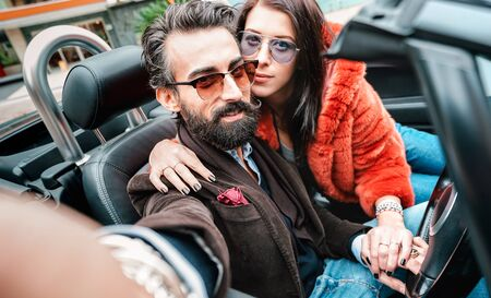 Cool feliz pareja tomando selfie en viaje en automóvil roadster - Hombre barbudo con hermosa mujer divirtiéndose en la experiencia de viaje por carretera - Concepto de lujo con personas que viajan juntas - Enfoque en la cara del chico inconformista Foto de archivo