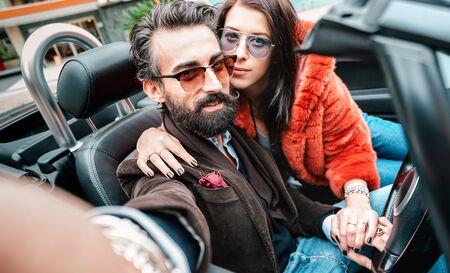 Cooles glückliches Paar, das Selfie bei Roadster-Autofahrt macht - Bärtiger Mann mit schöner Frau, die Spaß beim Roadtrip-Erlebnis hat - Luxuskonzept mit Menschen, die zusammen reisen - Fokus auf Gesicht des Hipster-Typen Standard-Bild