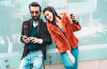 Modern hipster couple having fun using mobile smart phone outside - Social interaction concept with friends sharing digital content on social media networks - Millenial generation dating online