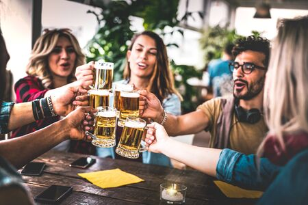 Friends toasting beer at brewery bar indoor at rooftop party - Friendship concept with young people having fun together drinking at happy hour promotion - Focus on glasses - Warm vignetting filter