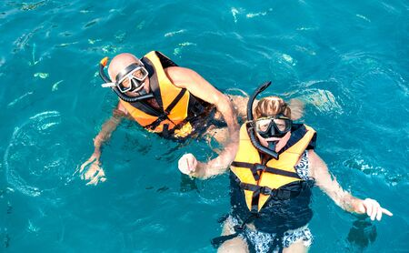 Senior couple posing for travel photo at snorkeling excursion in south east Asia during boat trip in exotic scenarios - Active retired elderly and fun concept around the world - Azure vivid filter
