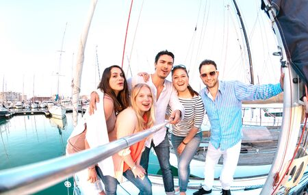 Friends group taking selfie pic with stick on luxury sailing boat party trip - Friendship concept with young millenial people having fun together at sailboat travel experience - Bright filter