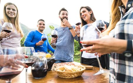 Friends group having fun at restaurant garden - Young people enjoying harvest time together at farm house vineyard - Friendship concept with millenials drinking red wine at outdoors winery on sunset