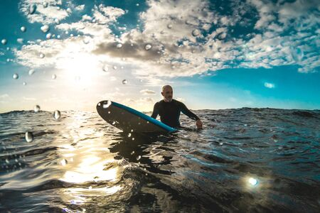 Surfer relaxing on surfboard at sunset in Tenerife waiting for the next good wave - Sport travel concept with shallow depth of field with drops on lens as composition - Contrast halo sunset filter Stock fotó