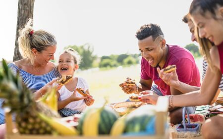 Cropped view of happy multiracial families having fun with kids at pic nic barbecue party - Multiethnic love concept with mixed race people eating with children at public park - Warm vivid filter