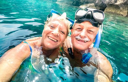 Happy retired couple with scuba mask taking selfie at tropical excursion - Boat trip snorkel experience in exotic scenarios - Elderly concept with active seniors traveling around world - Vivid filter
