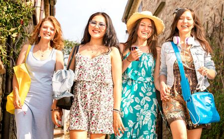 Multiracial millenial girlfriends walking at old town tour - Happy girls having fun around city streets - Friendship concept with women students on travel vacations - Warm afternoon vivid filter