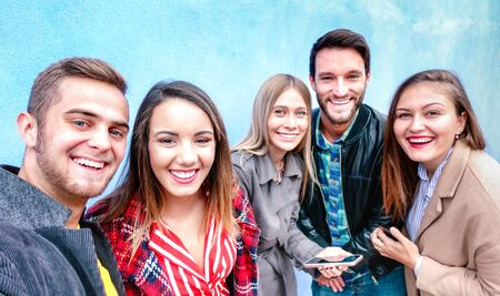 Best friends taking selfie wearing four seasonal clothes - Happy lifestyle concept with millenial people having fun together outdoors - Everyday life of next generation guys and girls on vivid filter