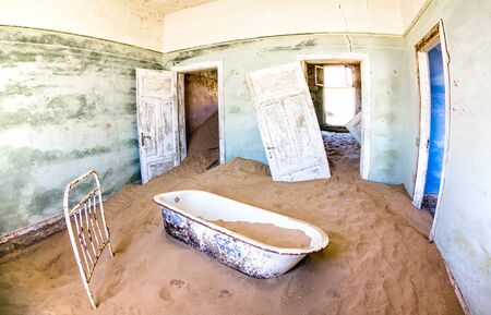 Abandoned house full of sand from the desert in the forsaken ghost town of Kolmanskop near Luderitz in Namibia - Wanderlust and travel concept exploring south african wonders - Vivid saturated filter Фото со стока