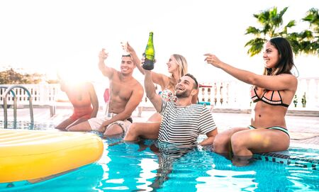 Happy friends cheering white wine champagne at swimming pool party - Luxury vacation concept with young guys and girls having fun together in summer day at hotel resort - Warm bright backlight filter Фото со стока - 142270314
