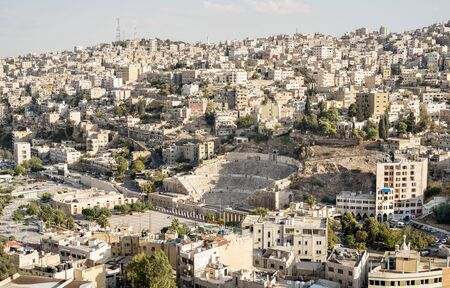 Aerial view of Amman city skyline with ancient roman theater ruins in Jordan - Travel wonder concept on middle east world famous destinations - Bright warm filter Фото со стока - 142271016