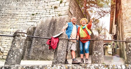 Senior retired couple having genuine fun in San Marino old town castle - Active elderly and travel lifestyle concept with mature people at italian roadtrip - Warm bright filter with soft sunshine halo