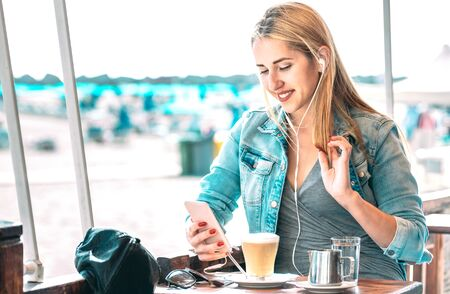 Young woman watching video on mobile smart phone at coffee bar - Fashion blogger girl sharing content while drinking latte - Modern wanderlust lifestyle concept on social media network - Azure filter Фото со стока - 142271020