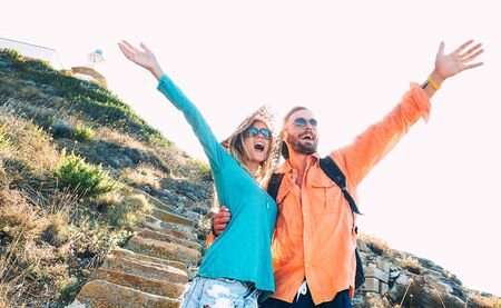 Happy boyfriend and girlfriend in love having genuine fun at travel excursion - Wanderlust life style and vacation concept with tourist couple at world trip on bright vivid filter