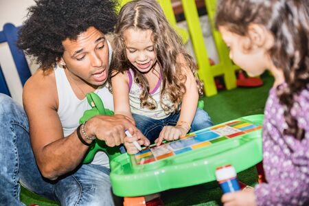 Latin american dad playing with mixed race daughter on educational skills at kindergarten playroom - Family concept with multiracial child and father having fun at kid school toyroom - Retro filter Фото со стока - 141224747
