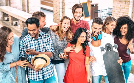 Cropped view of multiracial friends walking in city center - Happy guys and girls having fun at old town streets - University students on summer vacations after school end time - Bright vivid filter Stock Photo