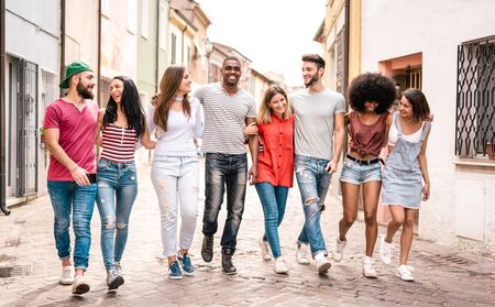 Multiracial millennial friends walking in city center - Happy guys and girls having fun around old town streets - University students on travel vacations  - Warm desaturated filter Фото со стока - 142271048