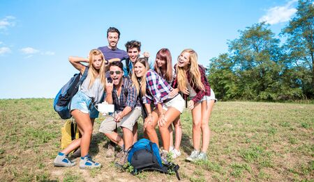 Friends group taking selfie at trekking excursion - Happy friendship and freedom concept with young millenial people having fun together at camping experience - Bright warm filter Фото со стока - 141306618
