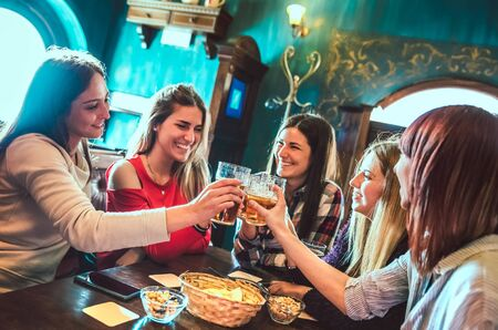 Happy girlfriends toasting beer at brewery bar restaurant - Female friendship concept with young women having genuine fun together at cool vintage pub - High iso filtered image with focus on glasses Фото со стока