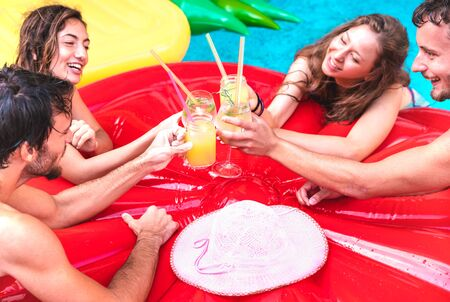 Cropped view of young people drinking fruit cocktails at pool party - Luxury vacation concept with guys and girls having fun in summer day at hotel resort - Happy friends cheering at tropical beach Фото со стока - 142271054