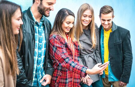 Millenial friends on addicted moment using mobile smart phones - Young people always connected at social media devices - Technology concept with modern teenagers sharing content online - Vivid filter Фото со стока - 142271055