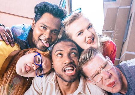 Multiracial millenial friends taking selfie sticking out tongue with funny faces - Happy friendship concept against racism with international young people having fun together - Bright vivid filter Фото со стока