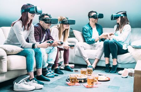 Friends playing with vr headset at home - Virtual reality and wearable tech concept with people having fun on 3d videogames - Generation z digital trends - Focus on left guy with bright azure filter