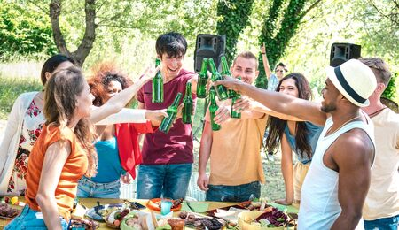 Happy multiracial friends toasting beer at barbecue garden party - Friendship concept with people having fun at backyard summer camp - Food and drinks dinner moment with dj music set - Warm filter Фото со стока