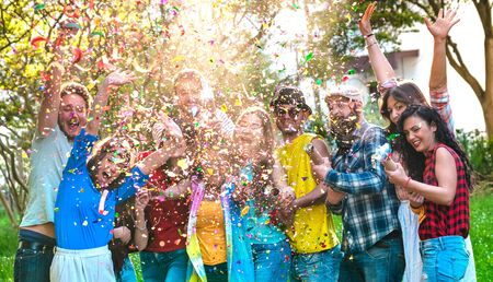 Happy excited friends having fun outdoor celebrating with confetti - Young millenial people enjoying summertime together at garden party - Cheerful friendship concept on warm vivid filtered color tone