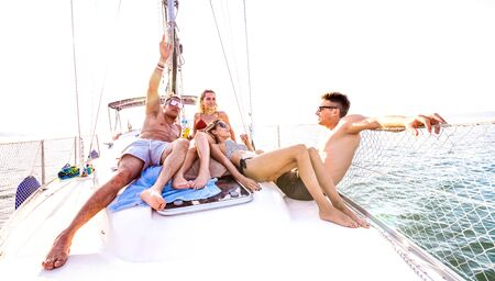 Front view of young millennial friends chilling on sailboat at sea ocean trip - Guys and girls having summer fun together at sail boat party day - Luxury excursion concept on bright vivid filter