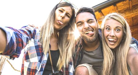 Friends trio taking selfie at trekking excursion - Happy friendship and freedom concept with young millenial people having fun together with funny faces on outdoors experience - Warm backlight filter Фото со стока - 142271070