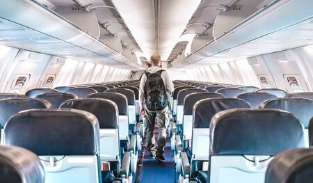 Inside view of commercial airplane with lonely man traveler - Emergency travel concept about flight cancellation - Aerospace industry crisis with empty plane on bright azure filter Фото со стока - 142271074