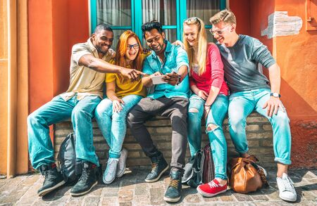 Multiethnic young people using smartphone at school building backyard - Happy friends on addict mood with mobile smart phones - Technology concept with trendy millenials on social media - Vivid filter Фото со стока