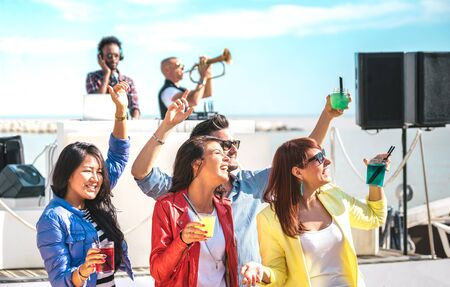 Young people dancing and having fun together at spring break festival - Deejay trumpet player entertaining happy friends at beach party - Dj playing at summer open air disco club - Bright vivid filter Фото со стока