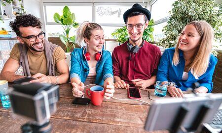 Digital native friends sharing video on streaming platform with web phone camera - Content marketing concept with millenial students having fun vlogging live feeds on social media space - Vivid filter Фото со стока - 142271099