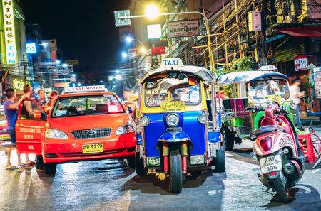 BANGKOK, THAILAND - 19 JANUARY 2015: street life and traffic with tuk-tuk rickshaw taxi near Khao San Road the beating heart of travelers movida in south east asia capital city - Vivid night filter