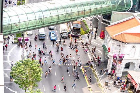 SINGAPORE - FEBRUARY 14, 2015: everyday life of people walking on zebra crossings under Orchard Road Gateway  - Crowded city center at rush hour in urban area - Street view from building top