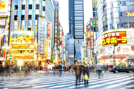 TOKYO - MARCH 2, 2015: everyday life with blurred commuters at rush hour on centra road in Kabuki district - International capital city with commercial ads in japanese language on landmark buildings Редакционное
