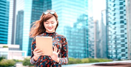 Young asian woman using electronic device at modern city  - Technology lifestyle concept with girl having fun with pc tablet device - Influencer digital trends on bright azure filter and sun halo Фото со стока - 142271117