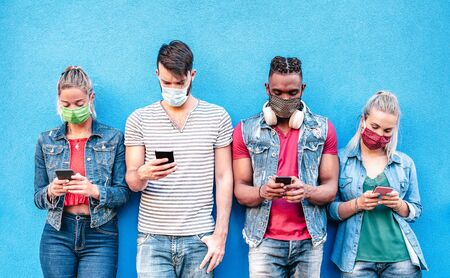 Multiracial friends with face masks using tracking app with mobile smart phones - Young millenial people sharing content on social media networks - New normal lifestyle concept - Bright vivid filter