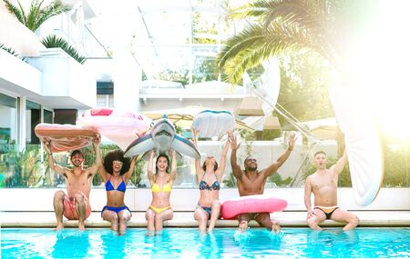 Front view of friends sitting at pool party with lilo airbed and swim wear - Summer lifestyle concept with happy guys and girls having fun in sunny day at luxury resort - Bright vivid sunshine filter Фото со стока - 148945238