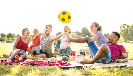 Happy multiracial families having fun with cute kids at pic nic garden party - Multicultural joy and love concept with mixed race people playing together with children at park - Bright sunny filter Фото со стока - 148564537