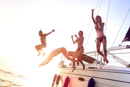 Young millenial friends jumping from sailboat at sea ocean trip - Guys and girls having summer fun together at sail boat party day - Luxury excursion concept on bright vivid filter with soft focus Фото со стока - 148564498