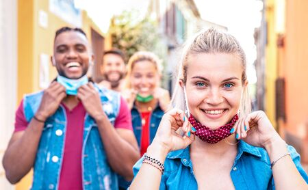 Multiracial friends smiling with face mask after lockdown reopening - New normal friendship concept with guys and girls having fun together on travel vacation - Bright filter with focus on right woman Фото со стока