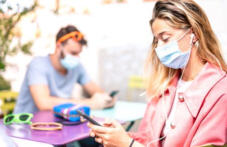 Young woman with earphones using tracking app on mobile smart phone - New normal everyday lifestyle concept with milenials sharing content at social media platforms - Bright filter with focus on girl Фото со стока - 149531754