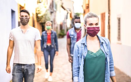 Multiracial friends walking with face mask after lockdown reopening - New normal friendship concept with guys and girls spending time together on city streets - Warm filter with focus on right woman