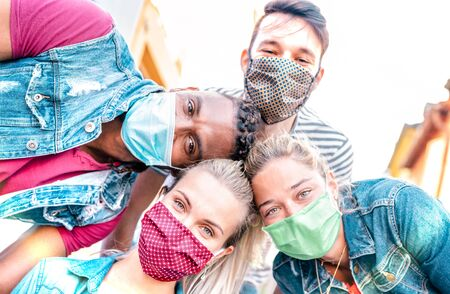 Multiracial millenial friends taking selfie smiling behind face masks - Happy friendship and new normal concept with young people having fun together - Bright sunshine filter with focus on left girl